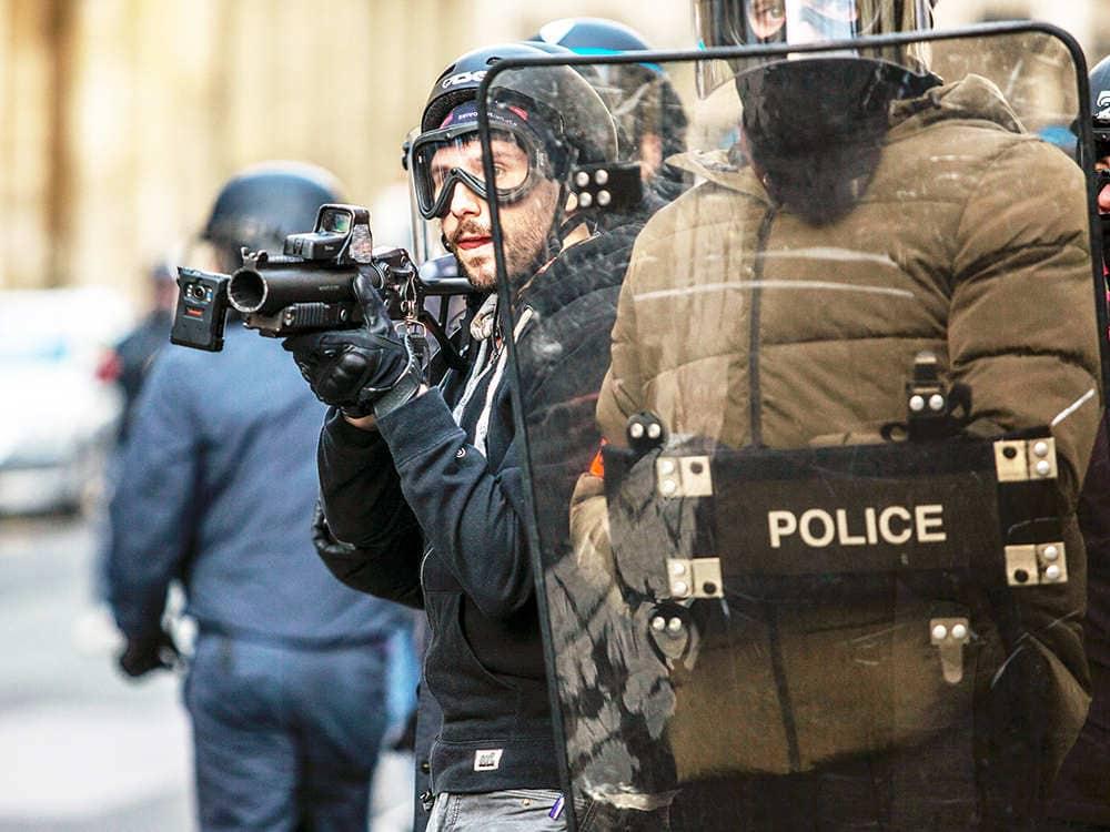 Zwei Polizeibeamte benutzen ein Schutzschild bei der Bekämpfung von Unruhen.