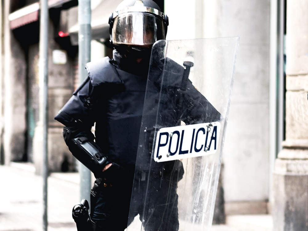 Französische Polizeibeamte verwenden Schutzschild zur Bekämpfung von Ausschreitungen.